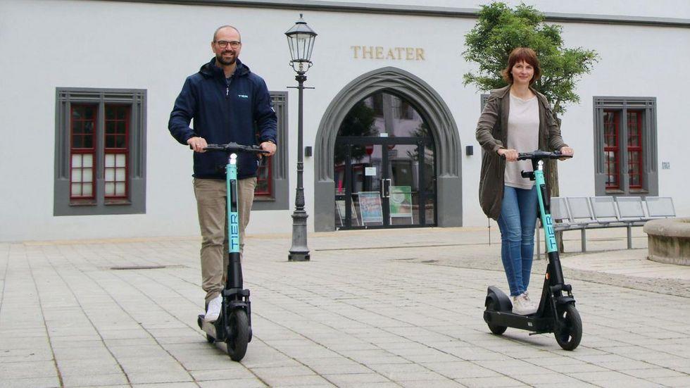 Sandra Hempel, Leiterin Büro Wirtschaftsförderung, und Georg Grams von Tier Mobility vorm Gewandhaus.