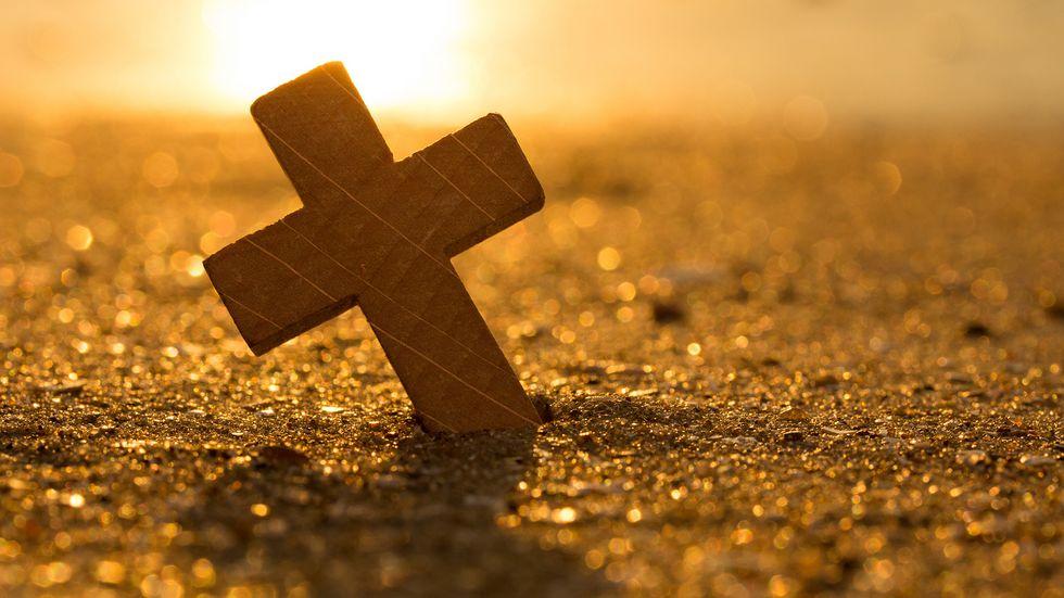 kleines Holzkreuz, steckt im Sand